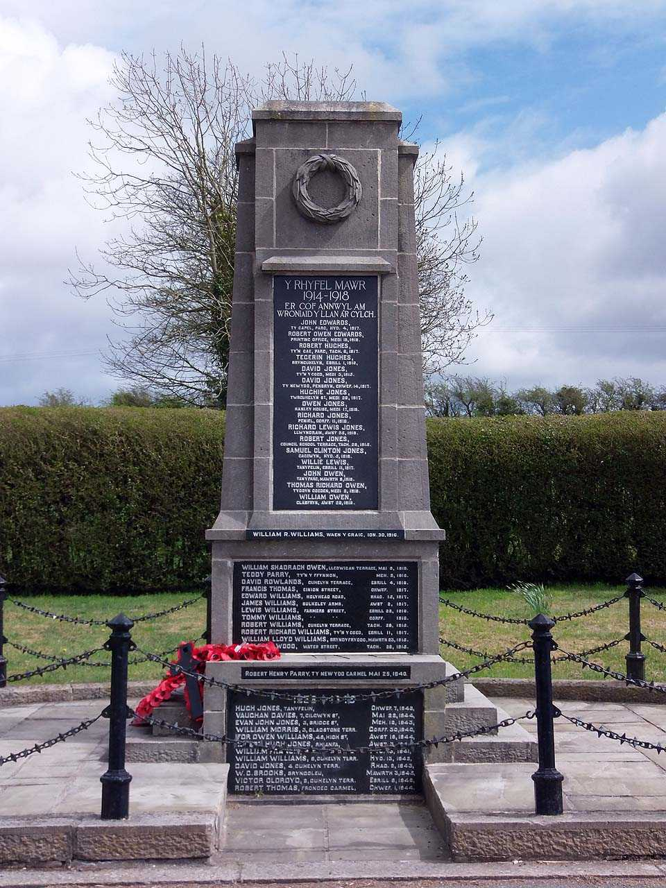 Llanerchymedd War Memorial. Concrete enclosed by black chains in a garden of remembrance.